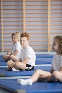 Kinder sitzen auf Matten