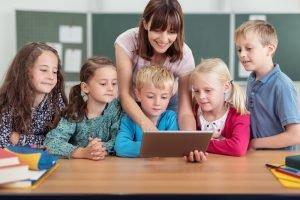Lehrerin zeigt kleinen Kindern etwas am Tablet