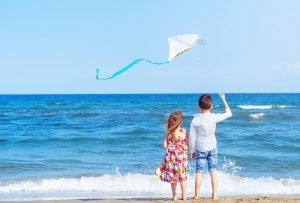 Kinder stehen am Strand und schauen aufs Meer