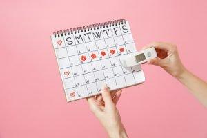 weibliche hand mit thermometer vor einem zykluskalender