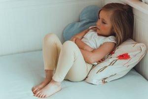 kleines Mädchen mit Bauchschmerzen in ihrem Bett
