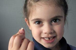 Mädchen mit ausgefallenem Milchzahn in der Hand