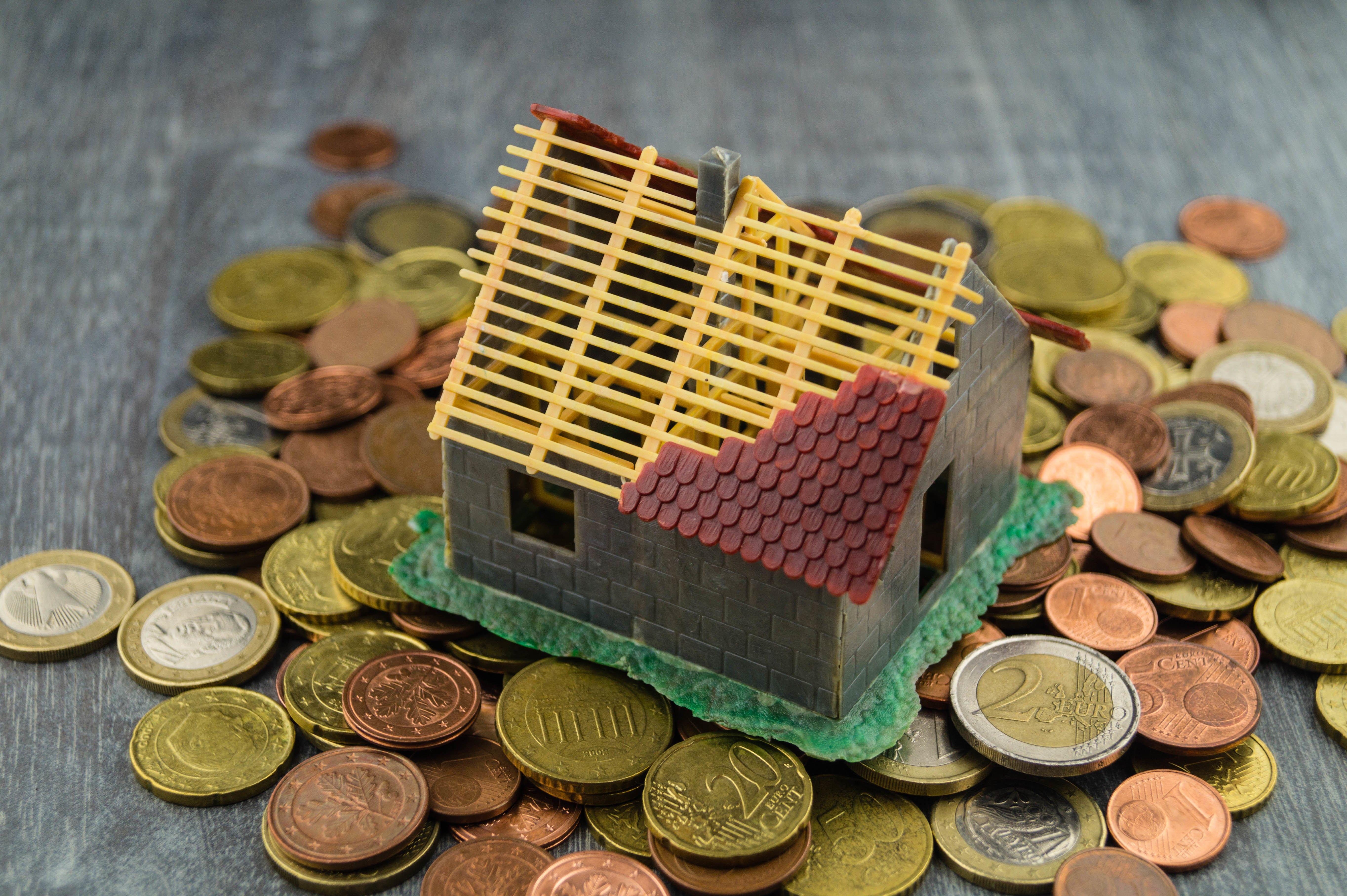 Miniaturhaus steht auf Kleingeld