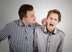 Vater zieht seinem Sohn am Ohr