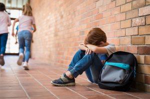 trauriger junge sitzt am boden in der schule