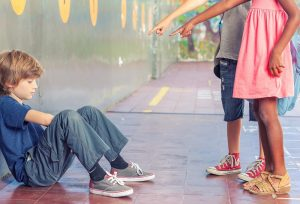 zwei kinder zeigen auf ein anderes kind und lachen
