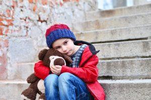 Kind umarmt Bär und ist traurig