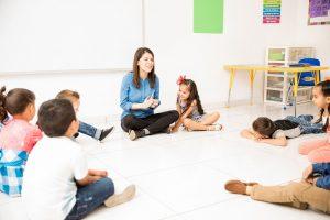 Kinder und Erzieherin sitzen im Kreis