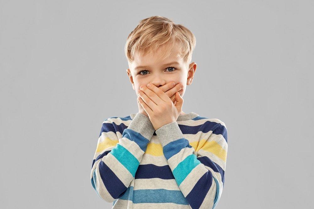 Kind hält sich mund zu