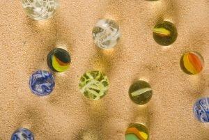 unterschiedliche murmeln liegen im sand