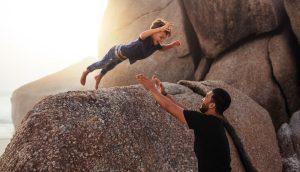 Sohn springt von einem Felsen in die Arme seines Vaters