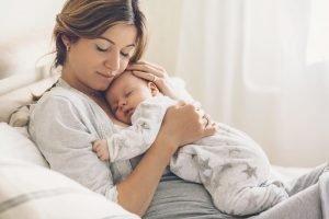 eine mutter haelt ihr baby im arm