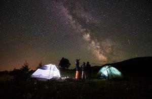 eine familie steht nachts neben zwei leuchtenden zelten und betrachtet den sternenhimmel