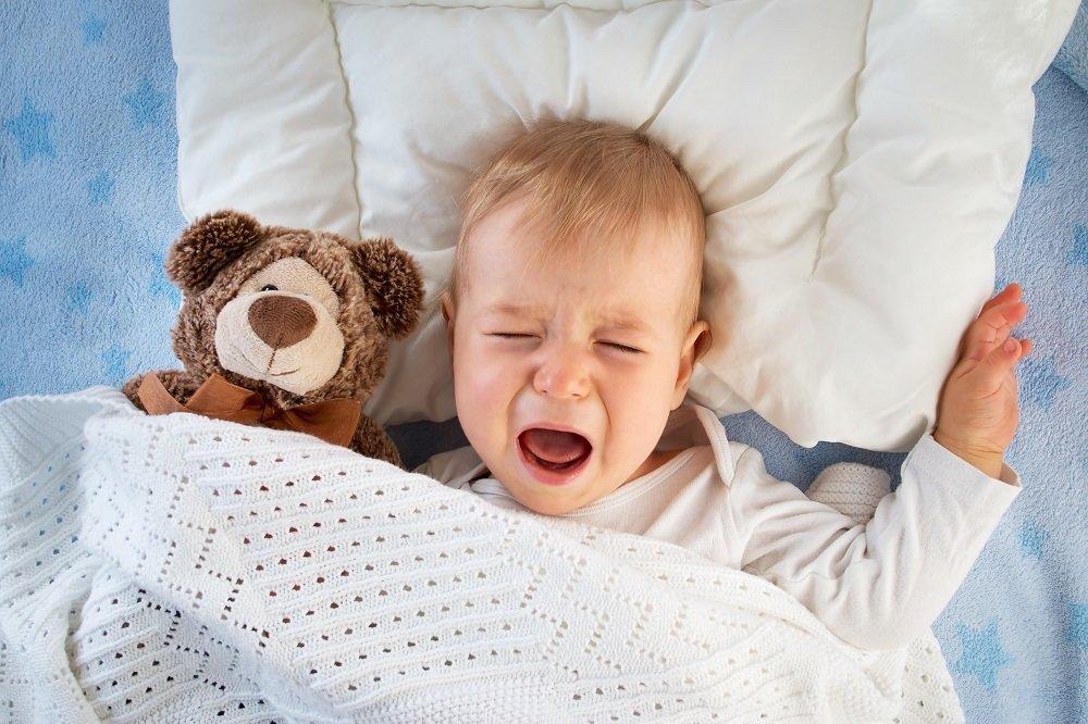 kind liegt mit teddy im bett und schreit