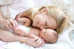 mutter kuschelt mit ihrem neugeborenen im Bett