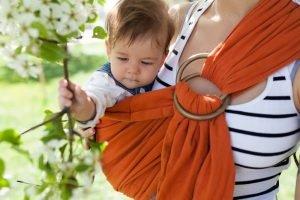 Kind wird beim Attachment Parenting nah an der Mutter getragen