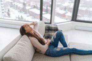 Frau liegt mit Kopfschmerzen auf der Couch