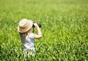 kleines Mädchen steht mit einem Fernglas im Gras