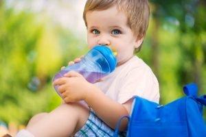 ein kleiner Junge trinkt Wasser aus einer Nuckelflasche
