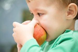 kleiner Junge isst einen Apfel