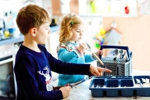 Kinder räumen gemeinsam die Spülmaschine aus
