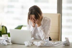 Frau sitzt verzweifelt am Schreibtisch
