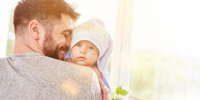 Stolzer Vater trägt sein Baby nach dem Baden im Handtuch herum