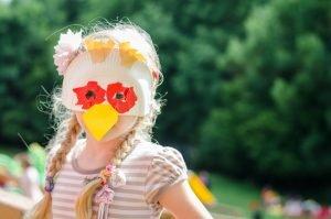 Kind mit einer Pappteller-Maske in Form eines Huhns
