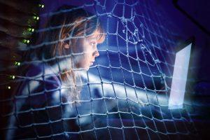 Kind sitzt im Dunkeln vor einem PC