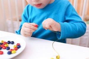 ein Junge fädelt Perlen auf eine Perlenkette