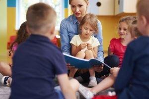 erzieherin liest kindern etwas vor