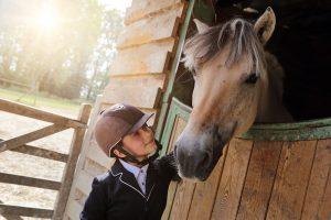 ein kind steht bei einem pferd an der box