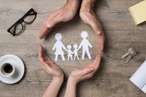 Hände werden im Kreis um eine aus Papier ausgeschnittene Familie gelegt
