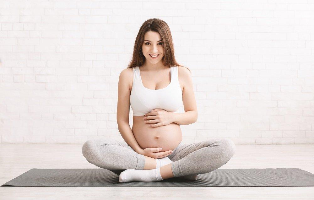 schwangere frau auf yoga matte