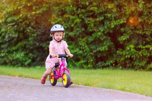 Mädchen fährt auf einem pinken Laufrad