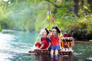 als Piraten verkleidete Kinder fahren auf einem Floß über einen Fluss