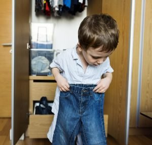 kleiner Junge hält eine zu kleine Hose vor sich