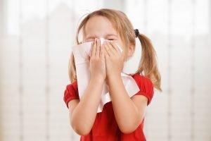 Kind schnaubt sich Nase