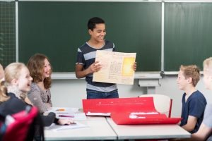 schueler stellt seiner klasse die ergebnisse einer gruppenarbeit vor