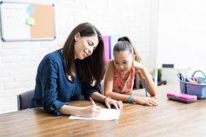 nachhilfelehrerin gibt einem maedchen nachhilfe