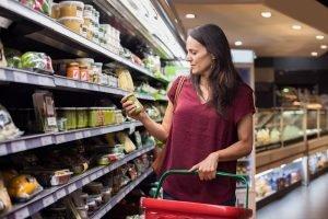 frau schaut im supermarkt auf ein etikett