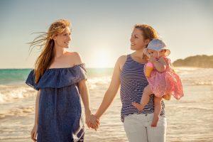 lesbisches Paar geht mit einem Kind am Strand spazieren