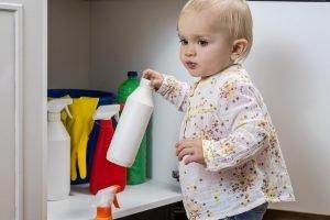 Säugling an einem Schrank mit Reinigern