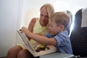 Mutter spielt zusammen mit ihrem Kind im Flugzeug ein Reisespiel