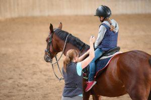 ein maedchen lernt auf einem pferd zu reiten