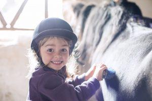 ein kleines Mädchen strigelt ihr Pferd
