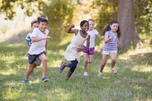 Kinder rennen über eine Wiese.