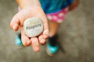 kind mit einem stein mit der aufschrift respekt in der hand