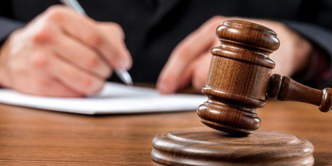 Schreibtisch mit Richterhammer im Hintergrund eine Person die schreibt