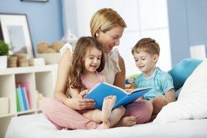 Mutter schaut mit Kindern ein Bilderbuch